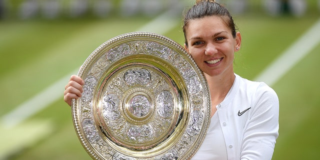 Simona Halep of Romania poise for a print with her prize after winning a Ladies' Singles final opposite Serena Williams of The United States during Day twelve of The Championships - Wimbledon 2019 during All England Lawn Tennis and Croquet Club on Jul 13, 2019 in London, England. (Photo by Mike Hewitt/Getty Images)