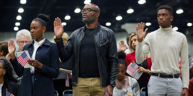 """Mixed martial arts great Anderson """"Spider"""" Silva of Brazil, center, his daughter Kaory, 23, left, and son Kalyl, 20, are is sworn in as a U.S. citizen along with thousands of others in a mass naturalization ceremony Tuesday, July 23, 2019 at the Los Angeles Convention Center. (AP Photo/Reed Saxon)"""