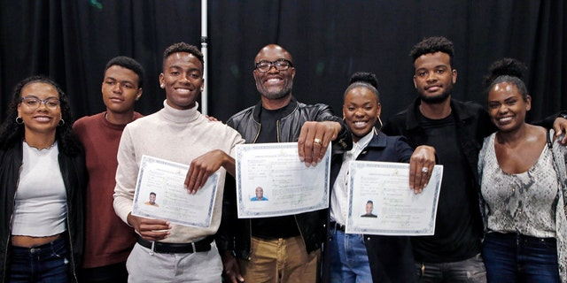 """Mixed martial arts great Anderson """"Spider"""" Silva of Brazil, center, his daughter Kaory, 23, right, and son Kalyl, 20, left, hold their citizenship documents after they are sworn in as U.S. citizens in a mass naturalization ceremony Tuesday, July 23, 2019 at the Los Angeles Convention Center. Joining them are family members who are not yet citizens, from left, daughter Kauana, 18; Joao, 14; and son Gabriel, 22, and Anderson Silva's wife Dayane. (AP Photo/Reed Saxon)"""