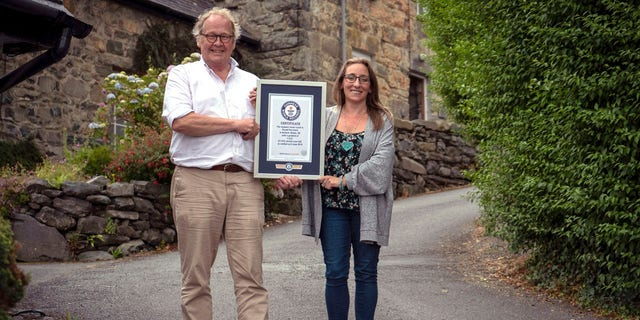 In this undated handout photo provided by Guinness World Records on Tuesday, July 16, 2019, Gwyn Headley and Sarah Badhan, stand on Ffordd Pen Llech with a certificate from Guinness World Records, confirming that the road is the steepest street in the world, in the seaside town of Harlech, North Wales.