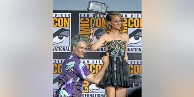 "Director Taika Waititi passes the hammer to Natalie Portman as they announce ""Thor 4: Love and Thunder"" at San Diego Comic-Con on July 20, 2019. Portman was previously believed to be done with the Marvel franchise."