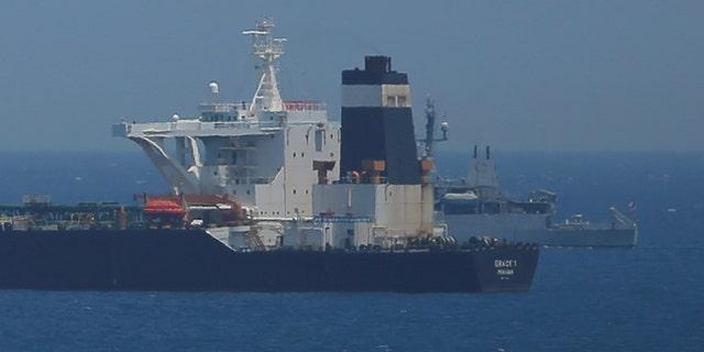 A British Royal Navy unit vessel guards a oil supertanker Grace 1.