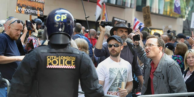 Police in riot gear watch Tommy Robinson supporters outside the Old Bailey courthouse in London on Thursday (AP/PA)