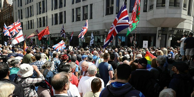 Tommy Robinson supporters stand outside the Old Bailey courthouse in London on Thursday, where clashes are reported to have become violent.
