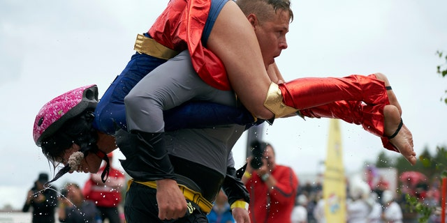 People take part in the wife carrying race, a 278-yard obstacle course, during the 24th world championships in Sonkajarvi, Finland, Saturday, July 6, 2019. (AP Photo/David Keyton)