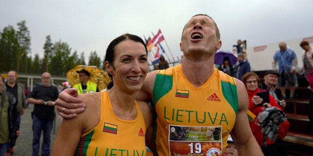 Lithuanian couple Vytautas Kirkliauskas, right, and Neringa Kirkliauskiene celebrate their victory in the wife carrying race, a 278-yard obstacle course, during the 24th world championships in Sonkajarvi, Finland, Saturday, July 6, 2019. (AP Photo/David Keyton)