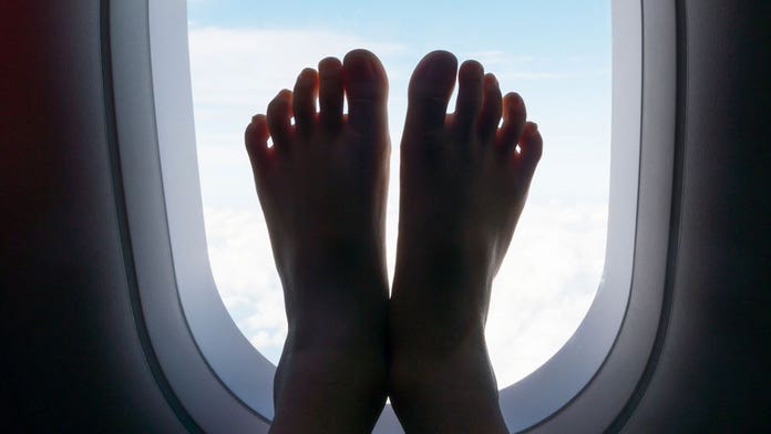 Video of airline passenger using feet to operate in-flight screen horrifies Twitter: 'I would open a side d...