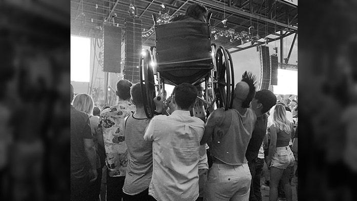 Weezer fan in wheelchair held up by concertgoers in North Dakota