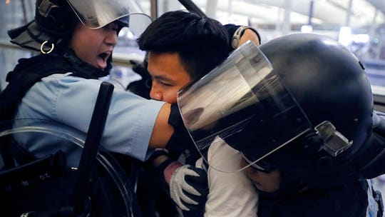 Hong Kong protesters clash with riot police armed with pepper spray at airport
