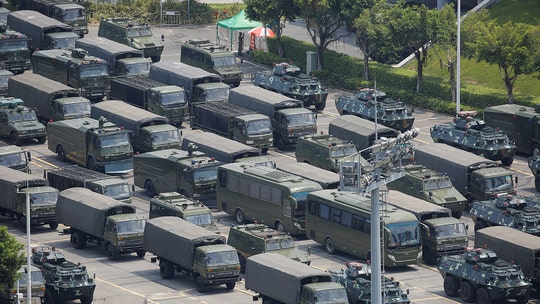 Chinese diplomat warns Beijing 'will not sit on its hands'; military runs drills near Hong Kong border