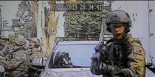 A security camera image provided by a neighbor who has requested not to be identified shows federal agents conducting a raid on the home of Paige A. Thompson in Seattle. (Associated Press)