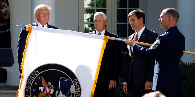 President Trump watches with Vice President Pence and Defense Secretary Mark Esper as the flag for U.S. Space Command is unfurled Thursday. (AP Photo/Carolyn Kaster)