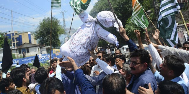 Pakistani Kashmiris carry an effigy of Indian Premier Narendra Modi during an anti-Indian protest in Muzaffarabad, capital of Pakistani Kashmir, Thursday, Aug. 8, 2019. Pakistan's federal minister for railways said Thursday that Islamabad has suspended a key train service with neighboring India over change in Kashmir's special status by New Delhi.
