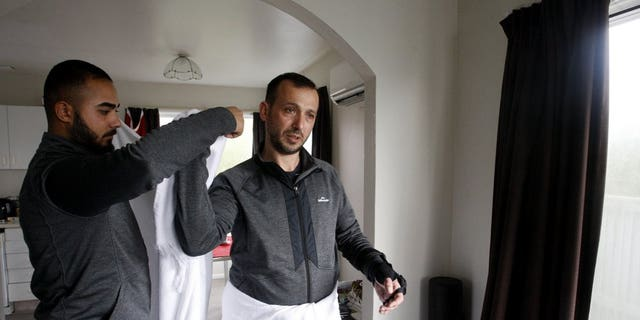 In this July 31, 2019, photo, Temel Atacocugu, who was shot nine times during the Christchurch mosque attacks, tries on the clothes he will wear during the Hajj pilgrimage, in Christchurch, New Zealand. He is among 200 survivors and relatives from the Christchurch mosque shootings who are traveling to Saudi Arabia as guests of King Salman for the Hajj pilgrimage, a trip many hope will help them to heal.
