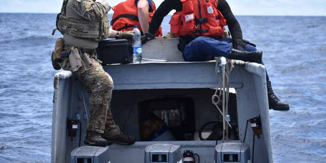 "Crew members from the pre-commissioned Coast Guard Cutter Midgett sitting atop the ""go-fast"" vessel. (U.S. Coast Guard)"