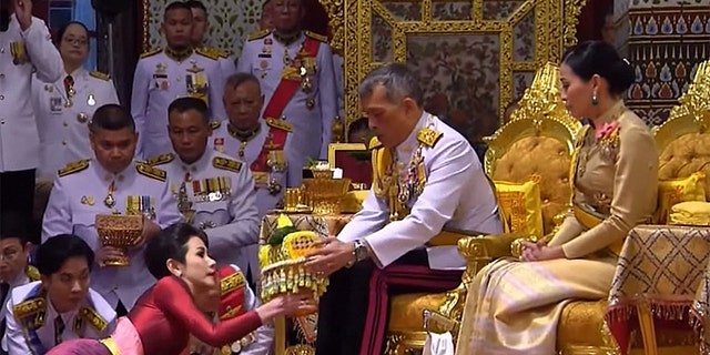 King Maha Vajiralongkorn (center), also known as King Rama X, sits alongside his wife General Suthida Vajiralongkorn (right) as he names Major-General Sineenat Wongvajirapakdi (left) the new Royal Noble Consort.