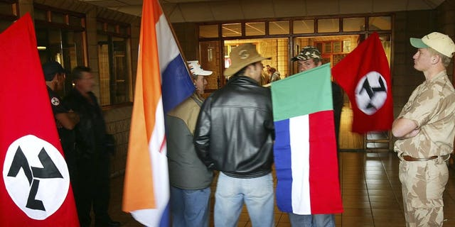 "Supporters of the Afrikaner Resistance Movement (AWB) display an old South African flag, second from left, an old Afrikaner ""Vierkleur"" flag and swastika-like flags as they await the release of their leader, Eugene Terre'Blanche from prison in Potchefstroom, South Africa where he was granted parole after serving three years of an effective five year sentence for the 1996 attempted murder of a black security guard."