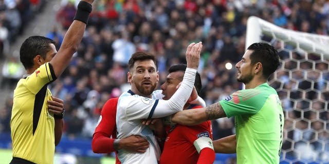 Argentina's Lionel Messi, center left, and Chile's Gary Medel, center right, scuffle as referee Mario Diaz, from Paraguay, left, shows the red card to both of them during Copa America third-place soccer match at the Arena Corinthians in Sao Paulo, Brazil, July 6, 2019. (Associated Press)