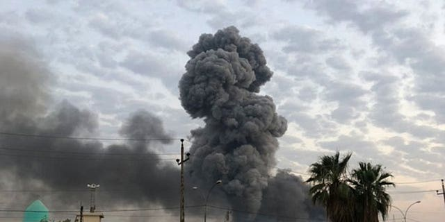 In this Monday, Aug. 12, 2019 file photo, plumes of smoke rise after an explosion at a military base southwest of Baghdad, Iraq. A fact-finding committee appointed by the Iraqi government to investigate a massive munitions depot explosion near the capital Baghdad has concluded that the blast was the result of a drone strike.
