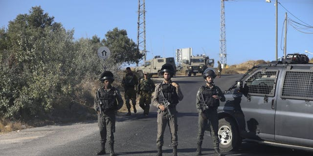 Israeli troops secure the area where a body of a soldier with stab wounds was found near Gush Etzion settlement in the West Bank, Thursday, Aug, 8, 2019.