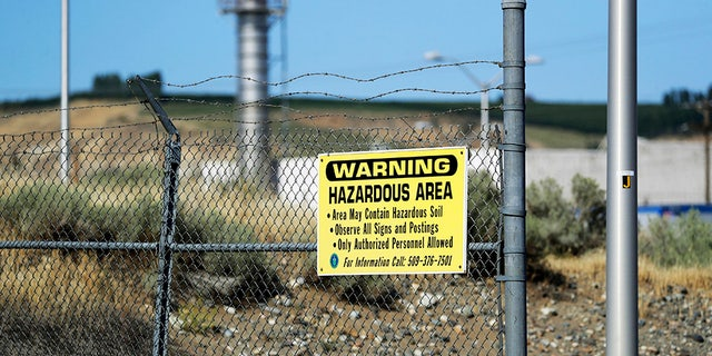 A sign at the Hanford Nuclear Reservation warning of possible hazards in the soil there along the Columbia River near Richland, Wash. (AP Photo/Elaine Thompson)