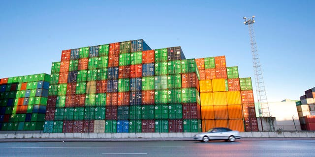 In this Monday, Nov. 24, 2014 file photo, a car drives by stacks of cargo containers at the Port of Antwerp, Belgium. Antwerp police announced Thursday, July 25, 2019 thay they have arrested two men who had called authorities to come rescue them from an overheated container in the port, where they had somehow locked themselves in, allegedly looking for drugs.
