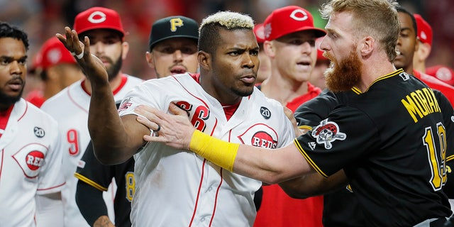 Cincinnati Reds' Yasiel Puig (66) is restrains by Pittsburgh Pirates third baseman Colin Moran (19) during the ninth inning of a baseball game Tuesday, July 30, 2019, in Cincinnati.