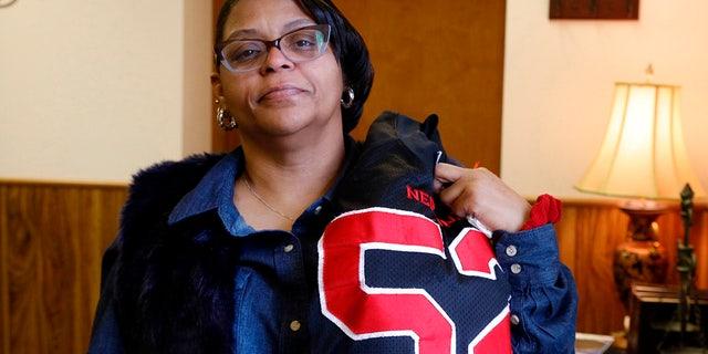JoAnne Atkins-Ingram drapes her late son's Neptune High School football jersey over her shoulder. (Doug Hood/The Asbury Park Press via AP File)