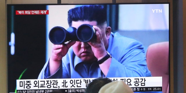 """People watch a TV showing a file footage of North Korean leader Kim Jong Un during a news program at the Seoul Railway Station in Seoul, South Korea, Friday, Aug. 2, 2019. The sign reads """"North Korea launches frequently."""" (Associated Press)"""