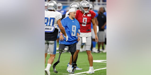 Calder Hodge, 14, of Magnolia, Texas, prepares to run a play with Detroit Lions quarterback Matthew Stafford during an open practice at Ford Field on Friday. Hodge was born without tibia bones but that hasn't stopped him from chasing his dreams of becoming a quarterback. Hodge wants to be the first quarterback with prosthetics. (AP Photo/Carlos Osorio)