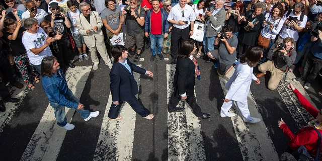 Thousands of fans gather to walk across the Abbey Road zebra crossing, on the 50th anniversary of the famous photo.