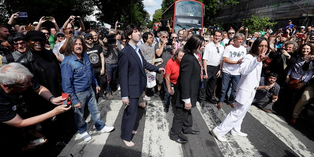 Fans dressed as look-alikes walk across the Abbey Road zebra crossing on the 50th anniversary of British pop musicians The Beatles doing it for their album cover of 'Abbey Road' in St Johns Wood in London, Thursday, Aug. 8, 2019.