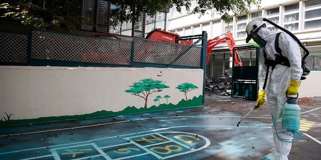 A worker sprays an adhesive product on the ground to gather up the lead particles in the schoolyard of Saint Benoit primary school in Paris, France, Thursday, Aug. 8, 2019. Workers have started decontaminating some Paris schools tested with unsafe levels of lead following the blaze at the Notre Dame Cathedral, as part of efforts to protect children from risks of lead poisoning. (AP Photo/Francois Mori)