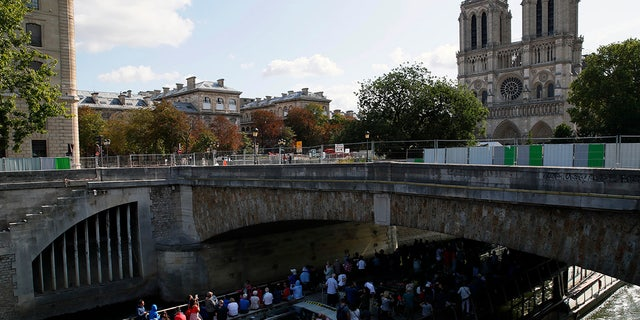 Tourists in a boat pass under a bridge near the Notre Dame cathedral in Paris, Tuesday, Aug. 13, 2019. Workers are preparing to decontaminate some Paris streets surrounding the Notre Dame Cathedral that have been tested with high levels of lead following the April blaze that damaged the landmark.