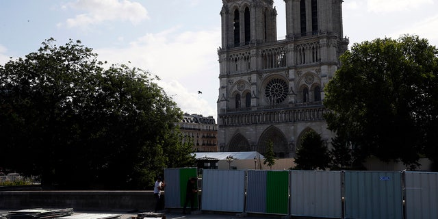 Workers install high fences on a bridge around Notre Dame cathedral in Paris, Tuesday, Aug. 13, 2019. Workers are preparing to decontaminate some Paris streets surrounding the Notre Dame Cathedral that have been tested with high levels of lead following the April blaze that damaged the landmark.
