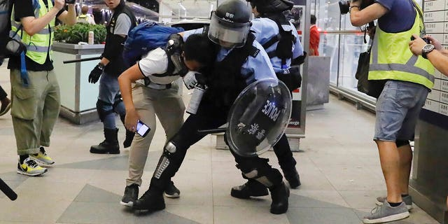Policemen in riot gear arrest a protester during a demonstration at the airport in Hong Kong, Tuesday, Aug. 13, 2019. Chaos broke out at Hong Kong's airport as riot police moved into the terminal to confront protesters who shut down operations at the busy transport hub for two straight days.