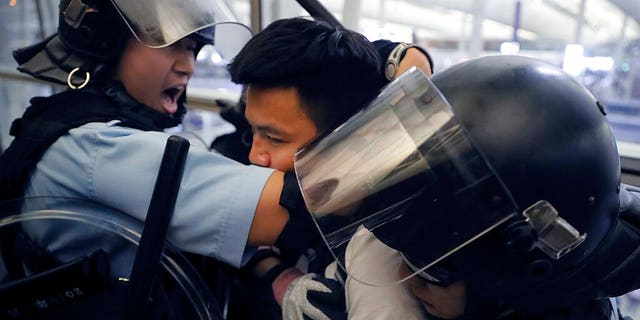 Policemen in riot gear arrest a protester during a demonstration at the airport in Hong Kong, Tuesday, Aug. 13, 2019.