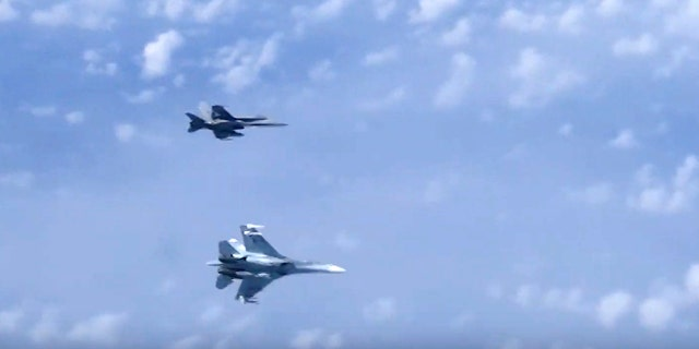 In this video grab taken from a footage on Aug. 13, 2019, and distributed by Russian Defense Ministry Press Service, a Russian air force's Su-27 fighter jet, bottom, maneuvers to ward off a NATO F-18 warplane over the Baltic Sea. (Russian Defense Ministry Press Service via AP)
