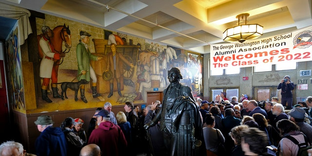 "People fill the main entryway of George Washington High School to view the controversial 13-panel, 1,600-square foot mural, the ""Life of Washington,"" during an open house for the public in San Francisco, Aug. 1, 2019. (Associated Press)"