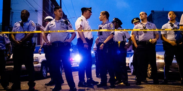 Officers gather for crowd control near a massive police presence set up outside a house as they investigate a shooting in Philadelphia, Wednesday, Aug. 14, 2019. (Associated Press)