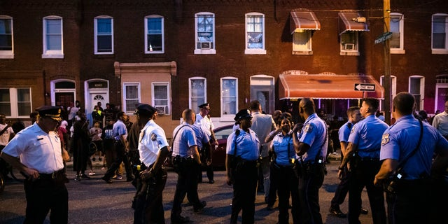 Officers gather for crowd control near a massive police presence set up outside a house as they investigate an active shooting situation, in Philadelphia, Wednesday, Aug. 14, 2019. (Associated Press)