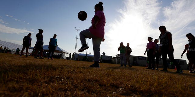 ​​​​​​​Immigrants play soccer at the U.S. government's holding center for migrant children in Carrizo Springs, Texas, July 9, 2019. (Associated Press)