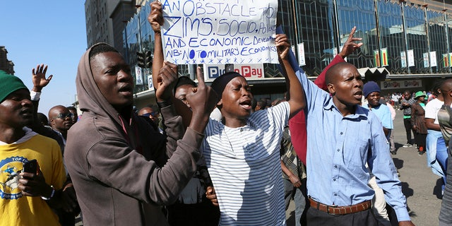 "Protestors gather on a street in Harare, Friday, Aug. 16, 2019. The main opposition Movement for Democratic Change party said it will roll out ""peaceful"" protests starting this week to try to force President Emmerson Mnangagwa to set up a transitional authority to address economic problems and organize credible elections. (AP Photo/Tsvangirayi Mukwazhi)"