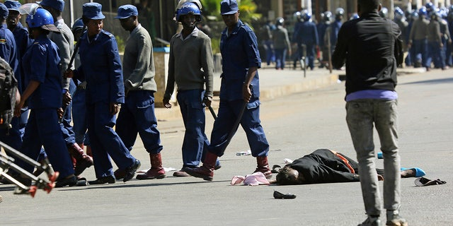 A woman lies in the road after being injured by police during protests in Harare, Friday, Aug, 16, 2019. The main opposition Movement For Democratic Change party is holding protests over deteriorating economic conditions in the country as well as to try and force Zimbabwean President Emmerson Mnangagwa to set up a transitional authority to address the crisis and organize credible elections. (AP Photo/Tsvangirayi Mukwazhi)