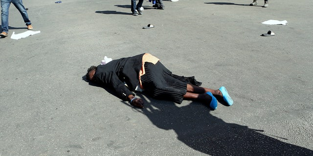 A woman lies injured on the tarmac after been injured during protests in Harare, Friday, Aug. 16, 2019. Zimbabwe's police patrolled the streets of Harare Friday morning while many residents stayed home and shops were shut fearing violence from an anti-government demonstration. Zimbabwe's High Court has upheld the police ban on the opposition protest. (AP Photo/Tsvangirayi Mukwazhi)