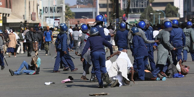 Riot police arrest and forcibly apprehend protestors during protests in Harare, Friday, Aug, 16, 2019. The main opposition Movement For Democratic Change party is holding protests over deteriorating economic conditions in the country as well as to try and force Zimbabwean President Emmerson Mnangagwa to set up a transitional authority to address the crisis and organize credible elections. (AP Photo/Tsvangirayi Mukwazhi)