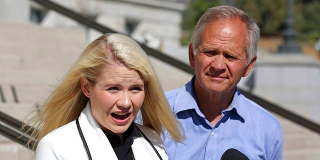 Elizabeth Smart speaks during a news conference while her father Ed Smart looks on, in Salt Lake City.