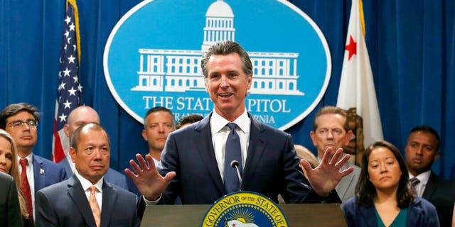 California Gov. Gavin Newsom, center, during a news conference in Sacramento, Calif., Friday, Aug. 16, 2019.