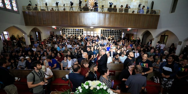 People offering condolences to Antonio Basco, lower right, at her funeral at La Paz Faith Memorial and Spiritual Center in El Paso this past Friday. (AP Photo/Jorge Salgado)