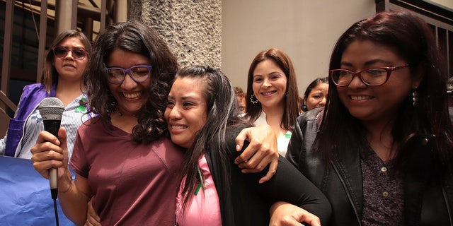 Evelyn Hernandez, 21, center, is embraced by supporters after being acquitted on charges of aggravated homicide in her retrial related to a pregnancy in 2016, in Ciudad Delgado, on the outskirts of San Salvador, El Salvador, Monday, Aug. 19, 2019.